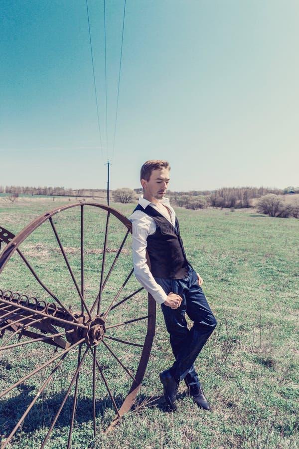 En ung man i en svart waistcoat och en vit svarta byxa för skjorta och står på fältet arkivbilder