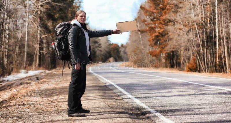 En ung man liftar runt om landet Mannen försöker royaltyfri fotografi
