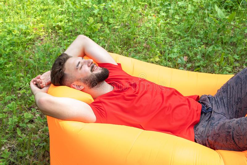 En ung man ligger på en luftmadrass, leenden, drömmar och vilar Angenäm tidsfördriv, avkoppling i natur arkivfoton