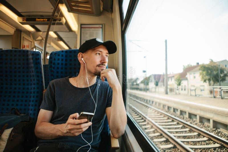 En ung man lyssnar till en musik eller en podcast, medan resa i ett drev royaltyfria foton
