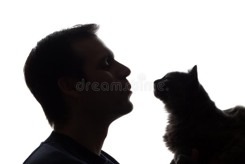 En ung man med en kattunge i hans händer royaltyfria bilder