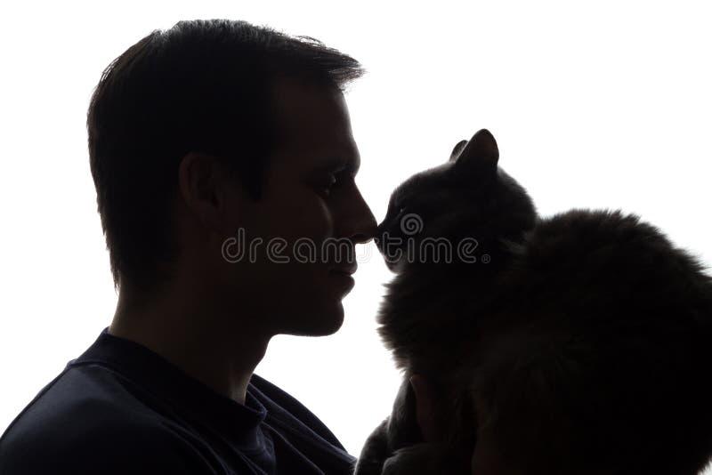 En ung man med en kattunge i hans händer arkivbild