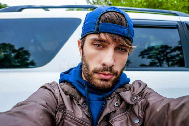 En ung man med ett framstående skägg poserar för en selfie som ser direkt in i linsen för kamera` som s bär en ljust marinblått h arkivfoto