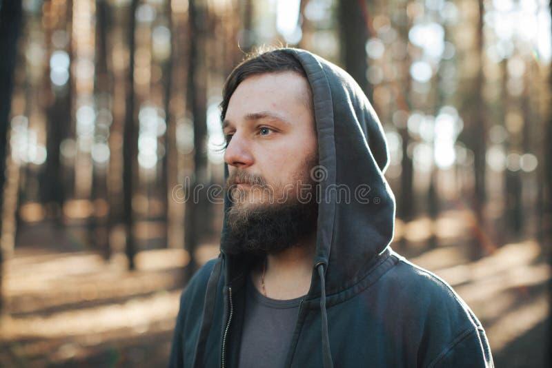 En ung man med ett skägg går i en pinjeskogstående av en brutal skäggig man i en huv royaltyfri fotografi