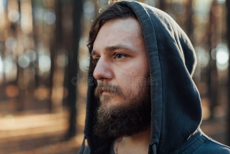 En ung man med ett skägg går i en pinjeskogstående av en brutal skäggig man i en huv arkivfoton