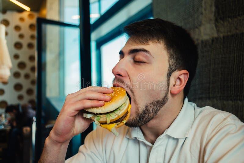 En ung man med ett skägg som äter en hamburgare på restaurangen och tycker om smaken arkivbild