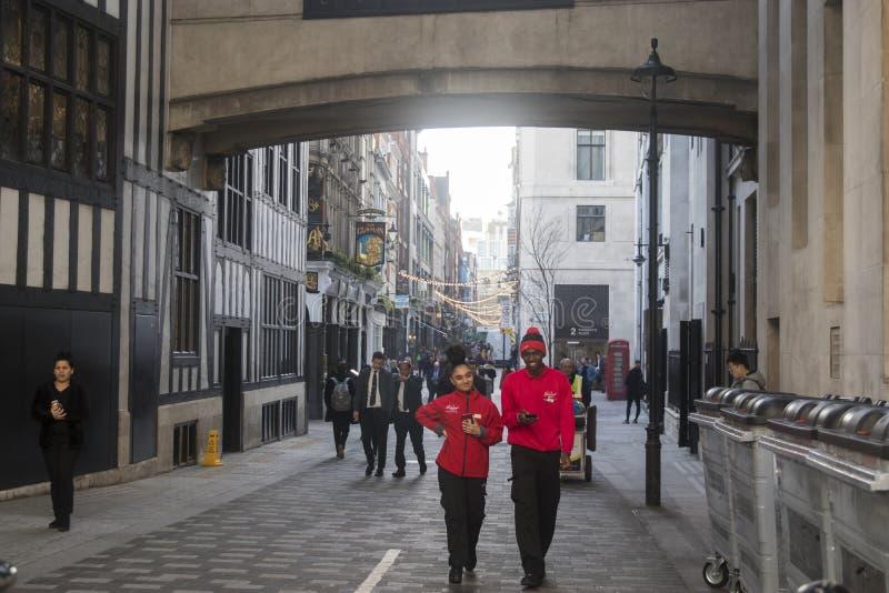 En ung man med en flicka i röda träningsoveraller som promenerar en fot- gata nära frihetlagret royaltyfri bild