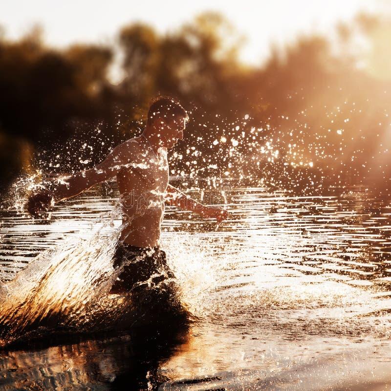 En ung man med en kal torso i svart kortsluter spring till och med vattnet med färgstänk mot solnedgången fotografering för bildbyråer