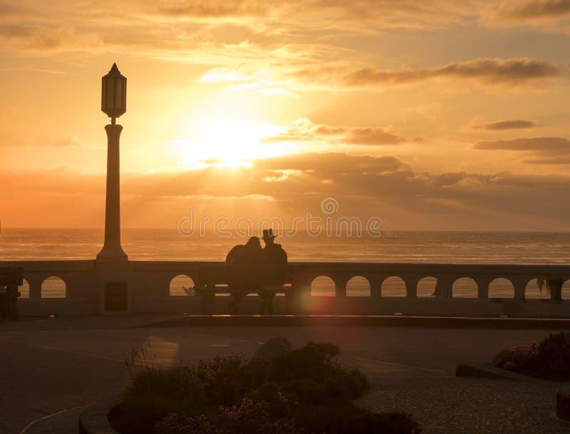 En ung man och ett förälskat sammanträde för kvinna på en bänk på kusten och att tycka om en härlig solnedgång arkivfoton