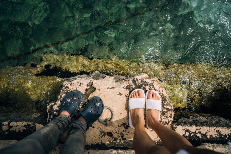 En ung man och en kvinna deras ben tillsammans över en pir royaltyfria foton