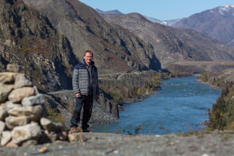 En ung man på banken av den Katun floden i Altai berg arkivfoton