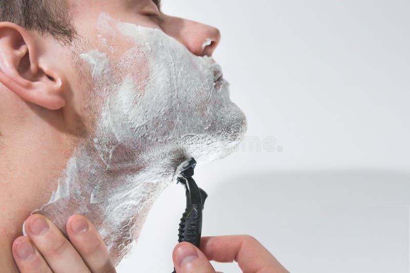 En ung man rakar hans skägg, rakbladet, hudomsorg, skum, royaltyfri foto