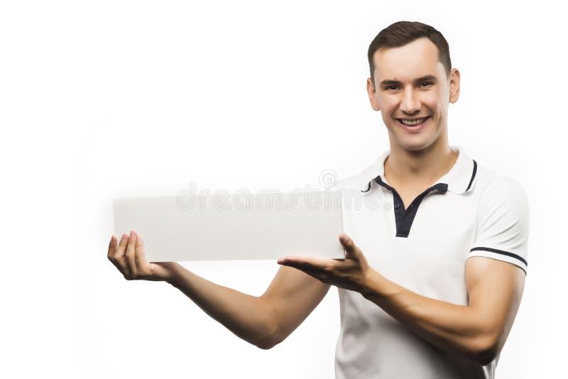 En ung man rymmer en tom platta i hans händer för att fylla din text arkivfoton