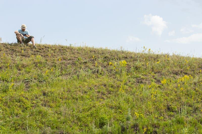 En ung man sitter överst av en kulle och blickar in i telefonen En turist vilar på en vandring, kontrollerade med en översikt i n royaltyfri bild