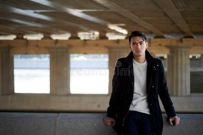 En ung man som är tunn Med ögon för mörkt hår och brunt Se kameran, stå under bron på floden folk in arkivbilder