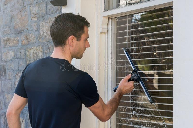 En ung man som använder yrkesmässig skrapa- och fönsterlokalvårdutrustning för att göra ren ett fönster arkivfoton