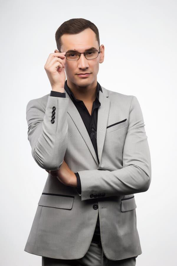 En ung man som bär en grå dräkt och exponeringsglas, rätar ut hans glas arkivfoton