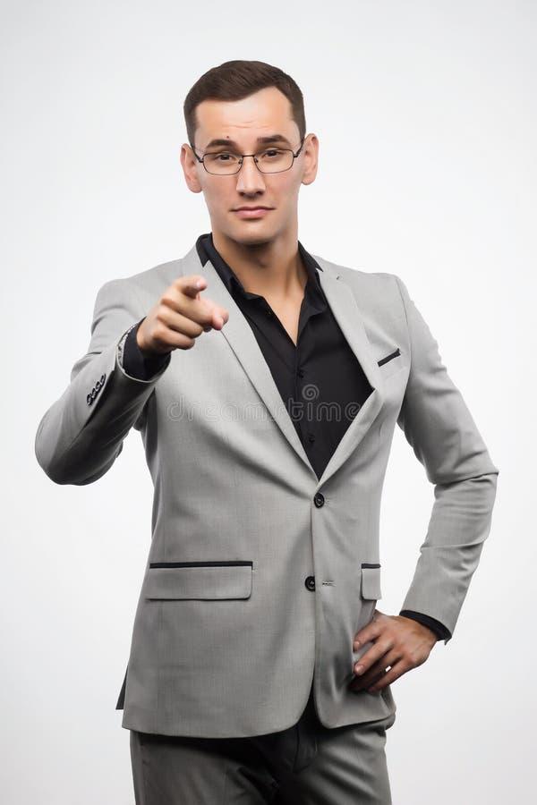 En ung man som bär en grå dräkt och exponeringsglas, visar ett teckenfinger royaltyfria bilder