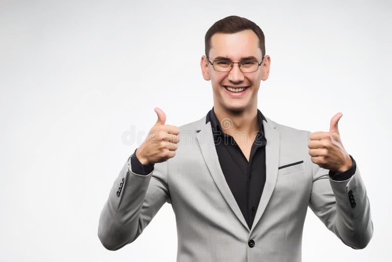 En ung man som bär en grå dräkt och exponeringsglas, visar en teckentumme u arkivfoton