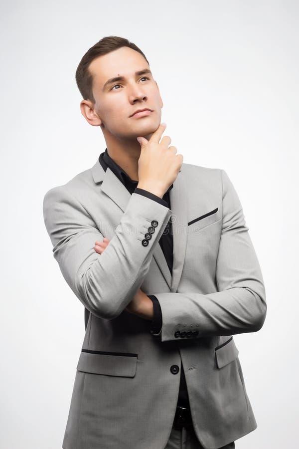 En ung man som bär grått tänka för dräkt arkivbild