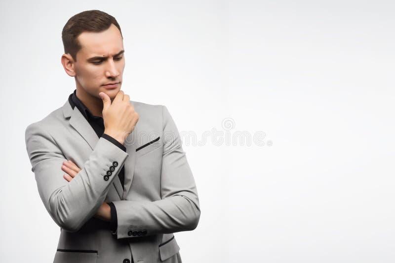 En ung man som bär grått tänka för dräkt arkivfoto