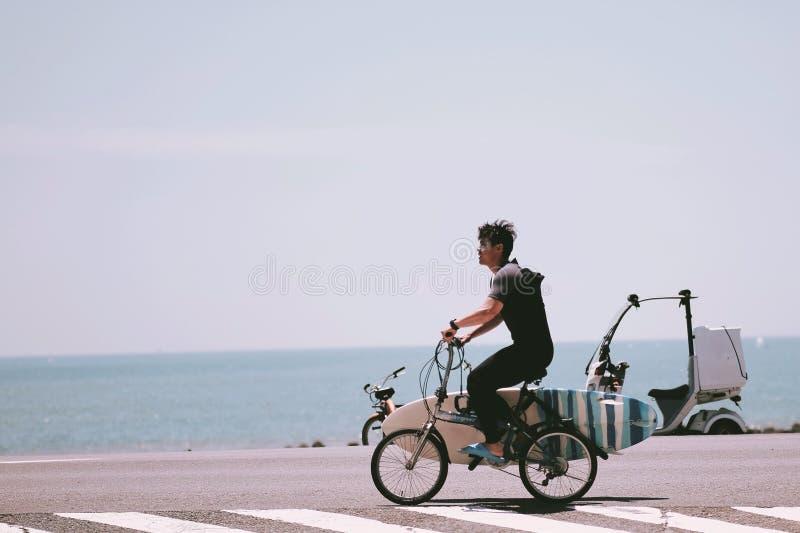 En ung man som cyklar för att surfa på havet royaltyfri bild