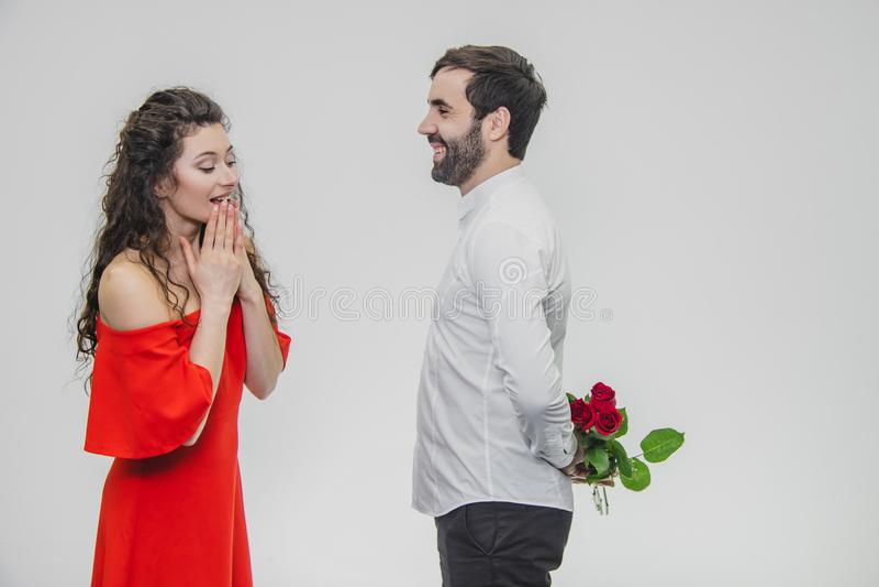 En ung man som döljer en grupp av rosor bak hans överraskning för att göra häpen hans flickvän för valentin dag fotografering för bildbyråer