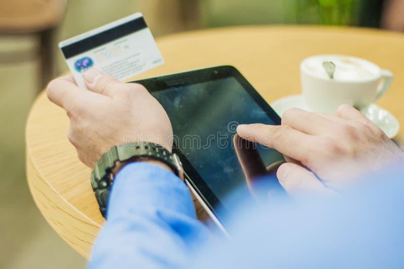 En ung man som direktanslutet shoppar med en kreditkort via en minnestavladator royaltyfri foto