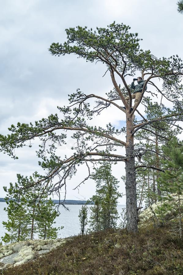 En ung man som klättras till överkanten av en höjdpunkt, sörjer på en stenig kust och kopplade av att se till och med kikare, mot royaltyfri bild