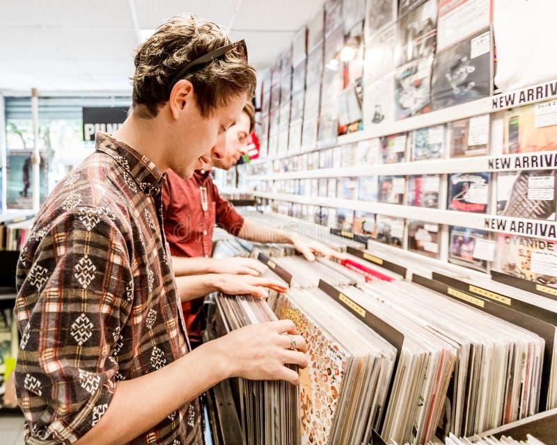En ung man som ser vinylrekord i ett lager eller att shoppa fotografering för bildbyråer