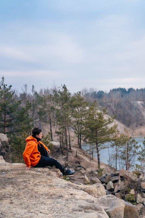 En ung man som sitter p? kanten av en klippa, poserar f?r kameran arkivfoton