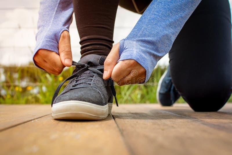 En ung man som tidigt på morgonen snör åt hans sko för en körning fotografering för bildbyråer