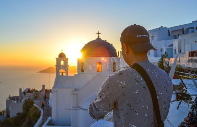 En ung man som tycker om på den Santorini ön arkivfoto
