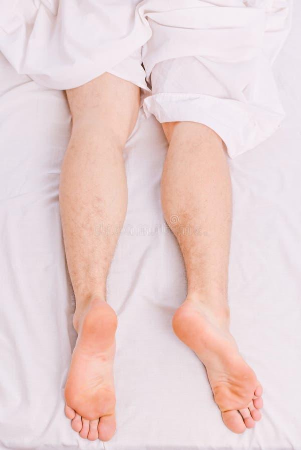 En ung man som vaknar upp i s?ng och str?cker hans armar Grabben ligger i s?ngen Morgon p? s?ng royaltyfria foton