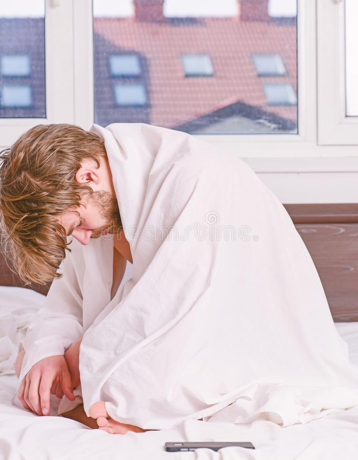 En ung man som vaknar upp i s?ng och str?cker hans armar Stilig man som g?spar upp och str?cker hans armar Lycklig morgon royaltyfri fotografi