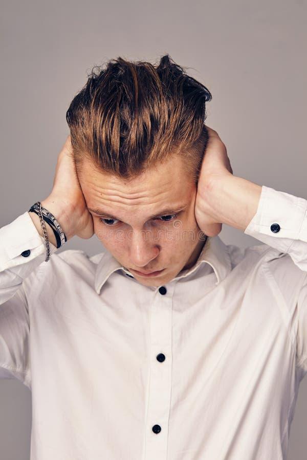 En ung man stänger hans öron arkivbild