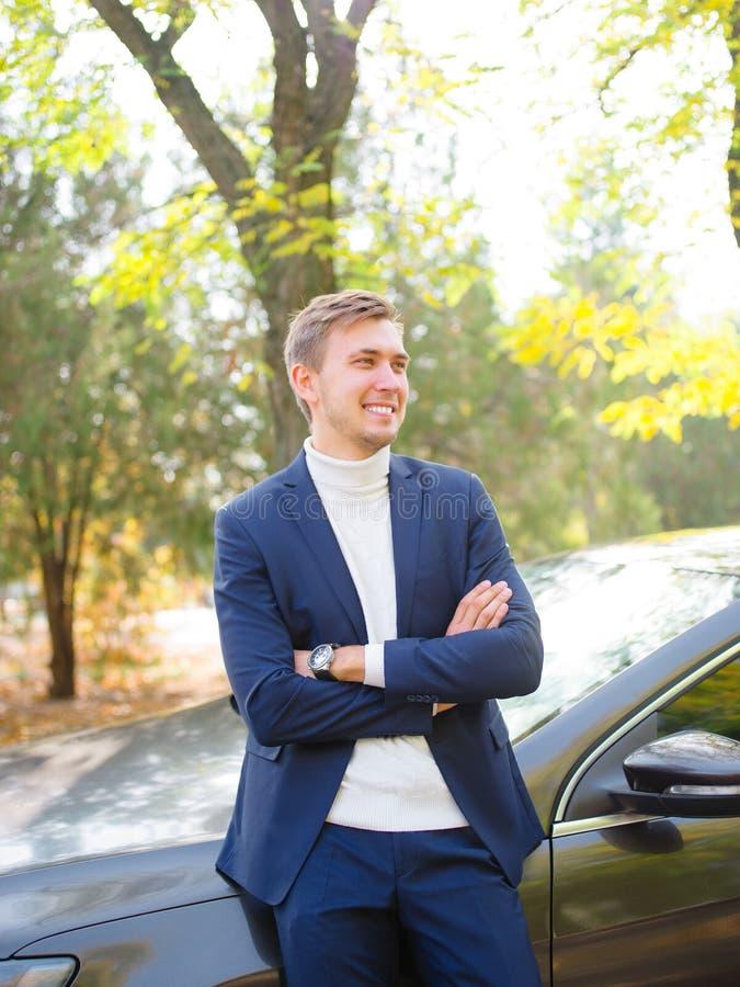 En ung man står i gatan nära bilen, ler och ser in i avståndet arkivbilder