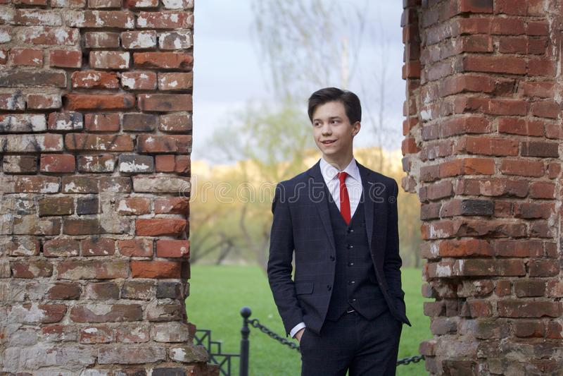 En ung man, en tonåring, i en klassisk dräkt Att grubbla står framme av den gamla väggen av röd tegelsten som sätter hans händer  royaltyfria bilder