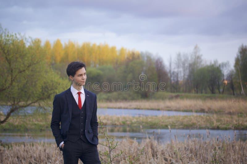 En ung man, en tonåring, i en klassisk dräkt Promenera avenyerna av våren parkera arkivbild