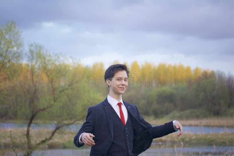 En ung man, en tonåring, i en klassisk dräkt Promenera avenyerna av våren parkera Vinka hans händer royaltyfri fotografi