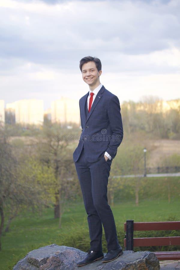 En ung man, en tonåring, i en klassisk dräkt Stå på en stor stenblock i en vår parkera och att sätta hans händer i hans fack royaltyfria foton