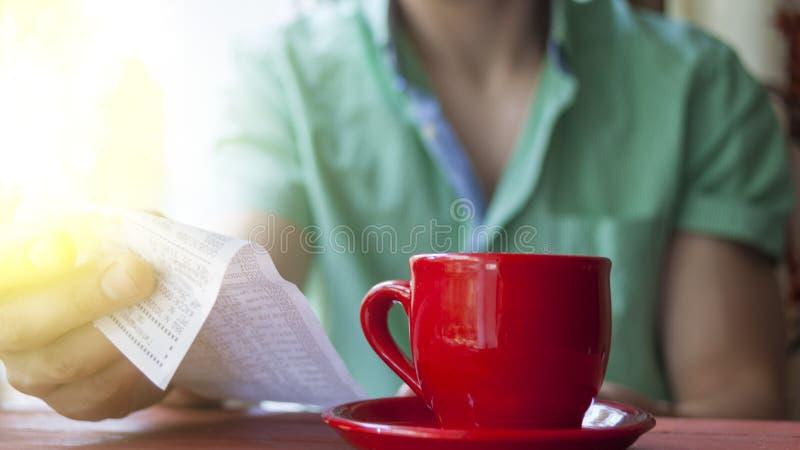 En ung man undersöker räkningen i ett kafé på en solig sommarmorgon arkivfoton