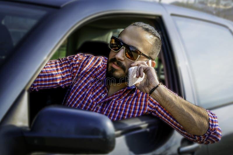 En ung manlig chaufför som talar på en mobiltelefon, medan köra en bil royaltyfri bild