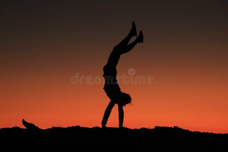 En ung manlig handelsresande står på hans händer och utför akrobatiska diagram på en bakgrund av ljust rött med orange himmel royaltyfri foto