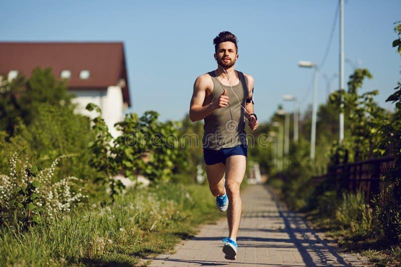 En ung manlig löpare joggar i parkera royaltyfria bilder