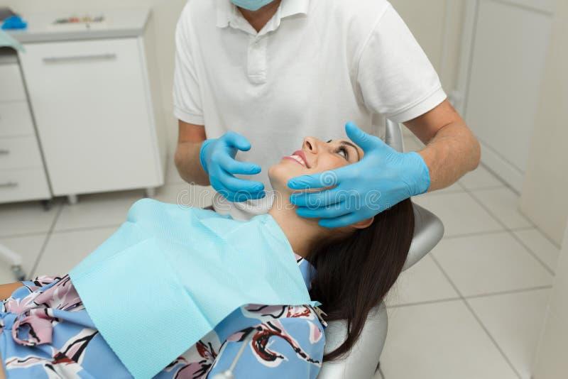 En ung manlig tandläkare och en lycklig kvinnlig patient Plats för tandläkarekontorslivsstil Doktorsövning Tålmodig hälsovård royaltyfria bilder