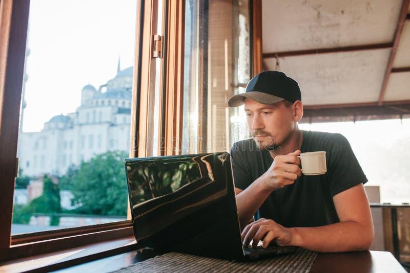 En ung manlig turist- bloggerfreelancer som arbetar på en bärbar dator i ett kafé i Istanbul En sikt från fönstret till världen royaltyfri foto