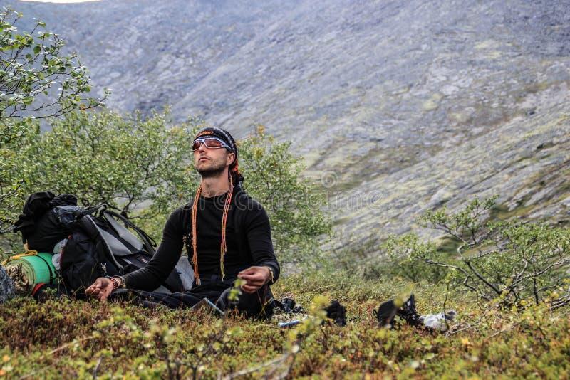 En ung manlig turist mediterar i bergen mot bakgrunden av bergen royaltyfria bilder