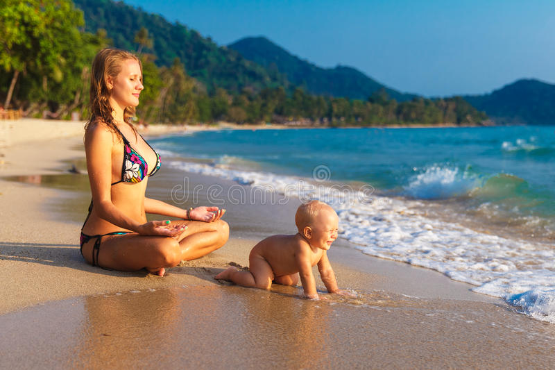 En ung moder med ett barn som har gyckel på en tropisk strand nat royaltyfria bilder