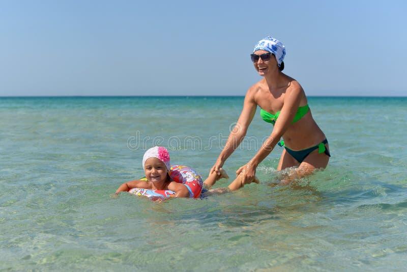 En ung moder med lite dotterbad i havet royaltyfri fotografi